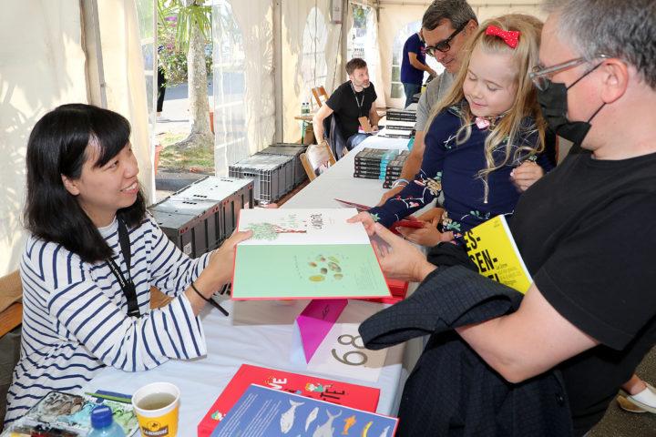 La petite Eva reçoit un livre dédicacé par l'autrice et illustratrice Aki . Photo: François Moesching